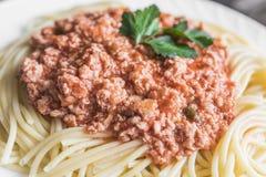 Espaguetis con la salsa de la carne en el cierre blanco de la placa para arriba Foto de archivo libre de regalías