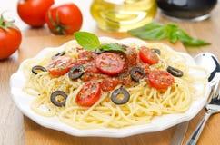 Espaguetis con la salsa de tomate, los tomates de cereza y las aceitunas fotos de archivo libres de regalías