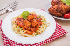 Espaguetis con las albóndigas en salsa de tomate y pollo frito fotos de archivo