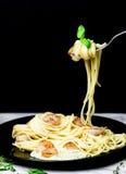 Espaguetis con los camarones girados en la bifurcación foto de archivo