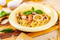 Espaguetis con los mariscos y el queso parmesano en placa beige fotos de archivo