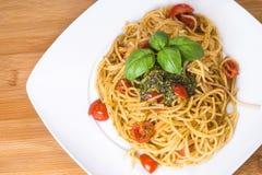 Espaguetis con los tomates de cereza y el pesto imagen de archivo