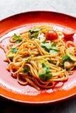 Espaguetis con los tomates, el avacado y el calabac?n, cocina vegetariana Fondo gris, visi?n superior, cierre para arriba fotos de archivo