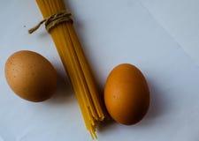 Espaguetis con una cuerda y huevos en el fondo blanco Fotos de archivo libres de regalías