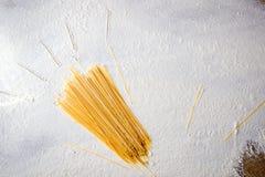 Espaguetis crudos de las pastas en fondo blanco floured Dé los haces exhaustos en la tabla, estilo simple del sol Fotos de archivo libres de regalías