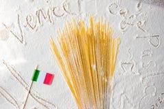 Espaguetis crudos de las pastas y primer italiano de la bandera en fondo blanco floured El viajar al concepto de la parte posteri Imagenes de archivo