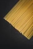 Espaguetis crudos en la placa negra Imagenes de archivo