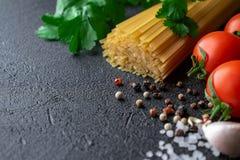 Espaguetis crudos en un fondo negro con los tomates, las especias y la sal gruesa del mar foto de archivo