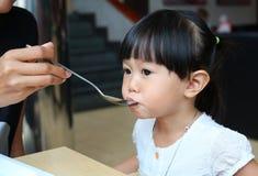 Espaguetis de alimentación de la madre en la cuchara para su niño fotos de archivo