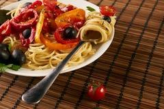 Espaguetis de las pastas con la salsa de tomate, las aceitunas, la paprika y las pimientas imagen de archivo libre de regalías