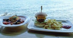 Espaguetis de los mariscos con la hamburguesa de la carne de vaca foto de archivo