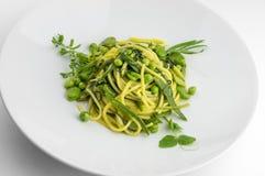 Espaguetis del plato de las pastas con las hierbas y los veggies de la primavera foto de archivo libre de regalías