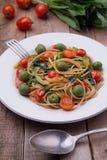 Espaguetis del trigo integral con los ramsons, los tomates y las aceitunas en la tabla de madera foto de archivo