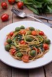 Espaguetis del trigo integral con los ramsons, los tomates y las aceitunas en la tabla de madera fotografía de archivo
