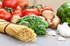 Espaguetis e ingredientes crudos para la salsa Imágenes de archivo libres de regalías