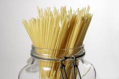 Espaguetis en el tarro de cristal en el fondo blanco Imagen de archivo