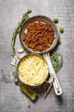 Espaguetis en la carne del cacerola y picada en una cacerola con las hierbas y el aceite de oliva Imagen de archivo