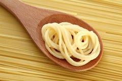 Espaguetis en una cuchara de madera Fotografía de archivo libre de regalías