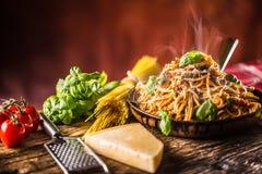 Espaguetis italianos de las pastas con albahaca del aceite de oliva de la salsa de tomate y queso parmesano en cacerola vieja foto de archivo
