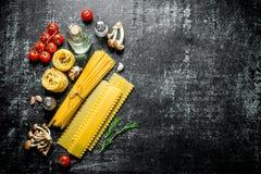 Espaguetis, lasa?as, tallarines crudos con aceite, tomates y setas fotografía de archivo