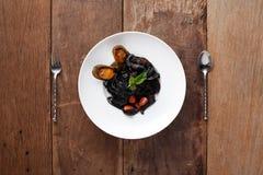 Espaguetis negros con los mariscos, preparados En la tabla Imagen de archivo libre de regalías