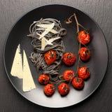 Espaguetis negros con los tomates y el queso parmesano cocidos Imagenes de archivo