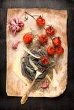 Espaguetis negros con los tomates y el queso parmesano cocidos Imágenes de archivo libres de regalías