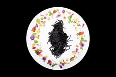 Espaguetis negros del calamar en placa con la decoración de la flor en fondo negro fotografía de archivo