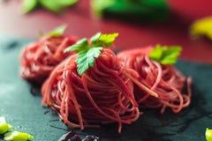 Espaguetis rojos con remolachas y habas verdes imagen de archivo