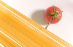 Espaguetis sin procesar con el tomate fresco imagen de archivo