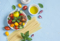 Espaguetis, tomates, albahaca, aceite de oliva - ingredientes crudos para cocinar las pastas vegetarianas En un fondo azul Imagen de archivo libre de regalías