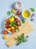 Espaguetis, tomates, albahaca, aceite de oliva - ingredientes crudos para cocinar las pastas vegetarianas En un fondo azul Fotos de archivo libres de regalías