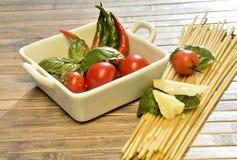 Espaguetis, tomates, albahaca y pimientos picantes Imagen de archivo