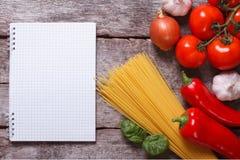 Espaguetis, verduras y especias y una libreta en la tabla vieja Imagen de archivo
