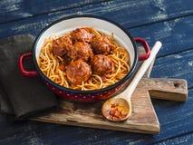 Espaguetis y albóndigas en salsa de tomate en tablero rústico de madera Fotos de archivo libres de regalías