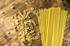 Espaguetis y estatuillas en un fondo de madera Foto de archivo libre de regalías