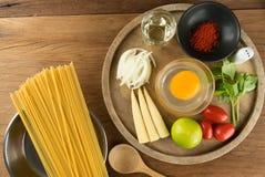 Espaguetis y huevos con la especia en el fondo de madera de la tabla para el cooki Imagen de archivo