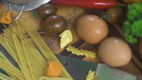 Espaguetis y macarrones italianos con los huevos frescos y la verdura cruda en la tabla de madera Ingrediente alimentario italian almacen de video