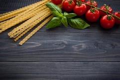 Espaguetis y tomates italianos de las pastas con las hierbas en una tabla de madera Imagen de archivo libre de regalías