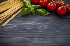 Espaguetis y tomates italianos de las pastas con las hierbas en una tabla de madera Fotografía de archivo