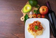 Espaguetis y vino rojo en la tabla de madera imágenes de archivo libres de regalías