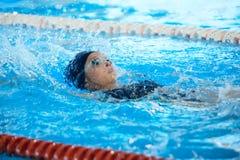 Espalda de la natación de la mujer joven en piscina Fotos de archivo libres de regalías