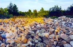 Espalhamento dos pedregulhos de pedra entre a grama e as árvores fora Fotos de Stock Royalty Free