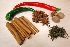 Espalhe belamente para fora pimentas vermelhas e verdes com especiarias em uma placa de corte Imagem de Stock