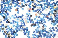 Espalhe botões azuis pequenos da costura em um fundo branco Fotos de Stock Royalty Free