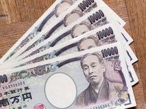 Espalhe o japonês conta de 10000 ienes na placa de madeira Imagens de Stock