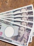 Espalhe o japonês conta de 10000 ienes na placa de madeira Fotografia de Stock