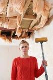 Espanador da terra arrendada da mulher sob o teto danificado Foto de Stock