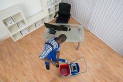 Espanador de Cleaning Floor With do guarda de serviço no escritório foto de stock