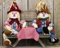 Espantalhos do menino e da menina que sentam-se na tabela de piquenique com sinal de madeira rústico vazio Imagem de Stock